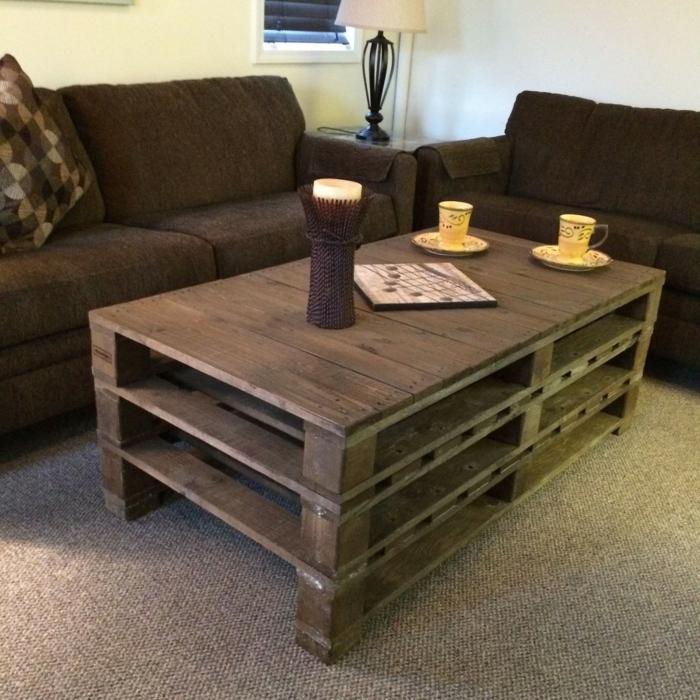 mesa para el salón de tres palets en color marrón oscuro con tazas de café encima y con vela