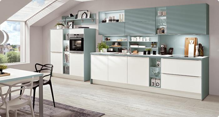 cocina con armarios en color blanco y azul claro con ventanas en el techo y con mesa en la alfombra