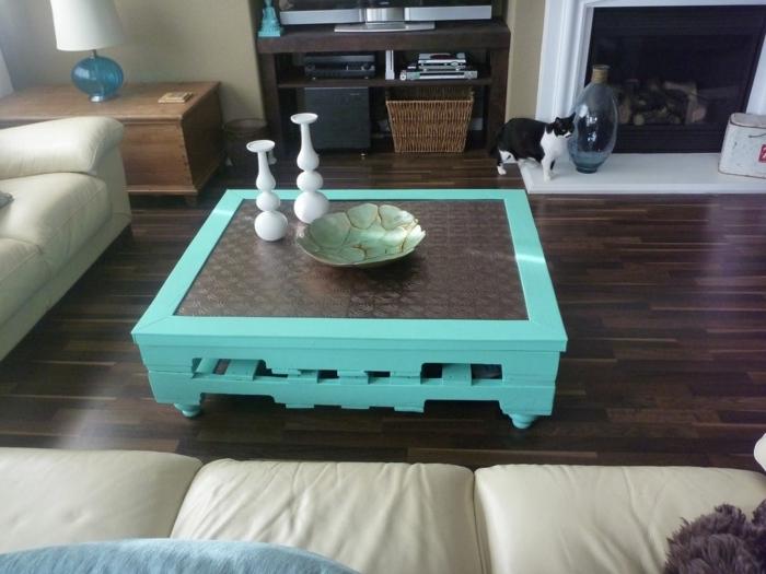 mesa de salon, muebles hechos con palets de color azul claro con vidrio grande encima y con patas de madera