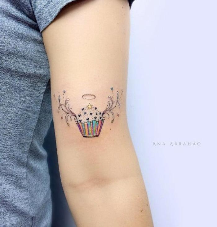 tatuajes en el brazo pequeños ideas simbólicas coloridas, muffin con alas angélicas en colores pastel