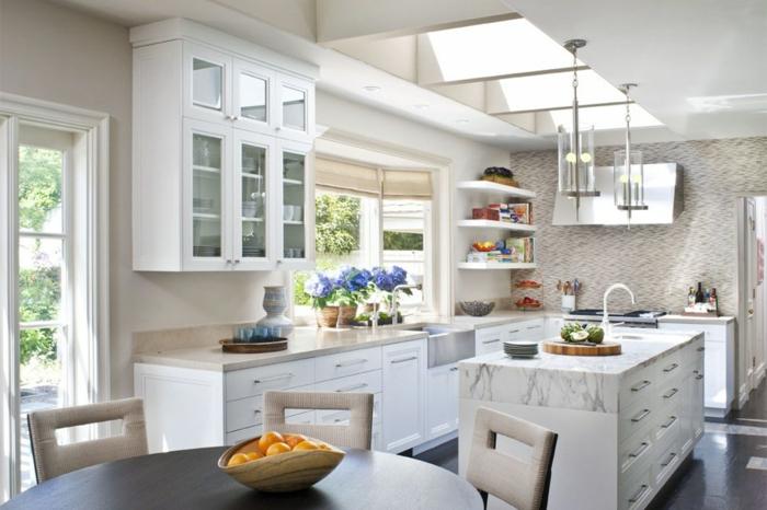 cocina de estilo americano en colores blancos con flores lilas en las ventanas y naranjas en la mesa