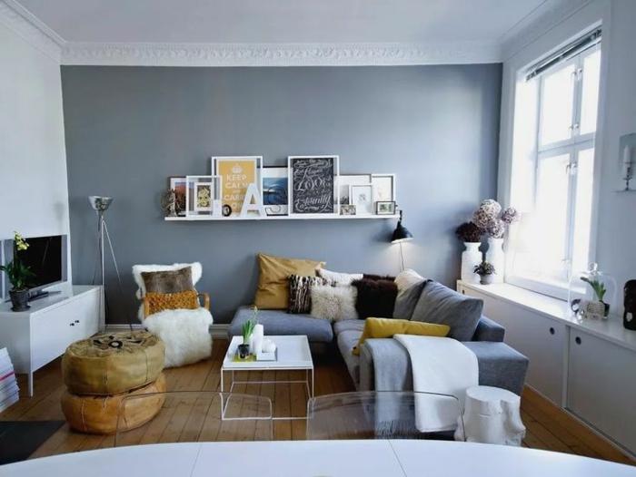 decorar salon pequeño cuadrado con una pared oscura en color azul y sofa pequeño con el mismo color