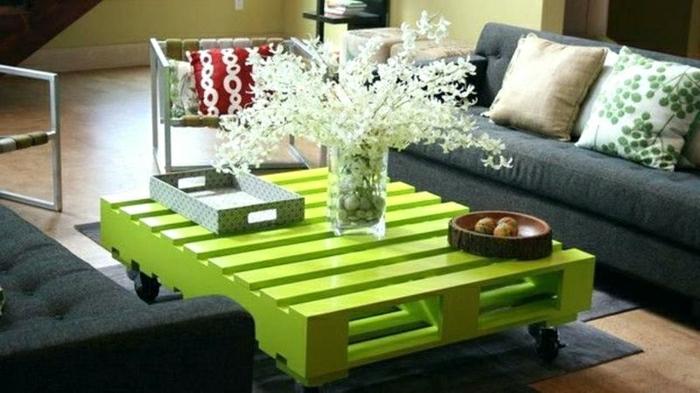 mesa de palets de color verde claro con ruedas y con sitio para revistas, jarrón cuadrado con flores vivas