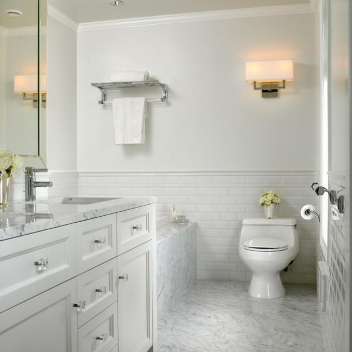 aseos pequeños decorados en blanco, bonita iluminación y bañera en estilo tradicional