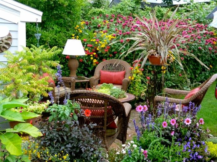 ideas de decoracion de jardines pequeños, rincón de relax con muebles de ratan y muchas flores