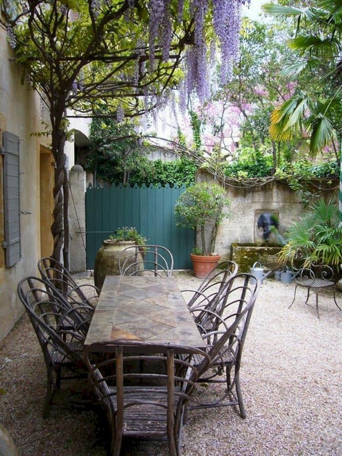 jardin mediterraneo de maravilla, muebles rústicos, suelo de gravilla y muchas plantas verdes