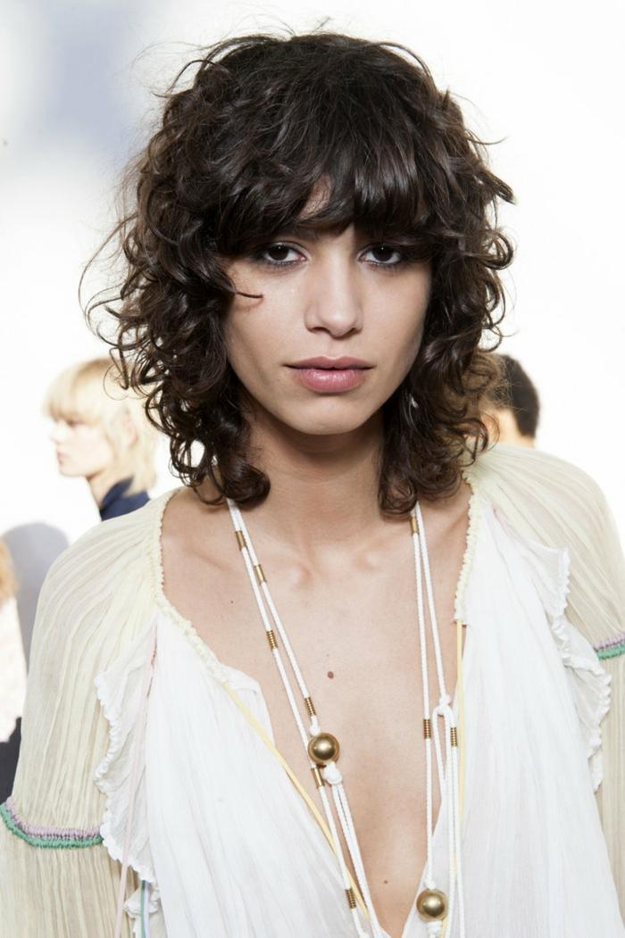 peinado pelo corto mujer, modelo con melena midi rizada con flequilloy vestido con escote profundo de seda en blanco y color crema, estilo boho