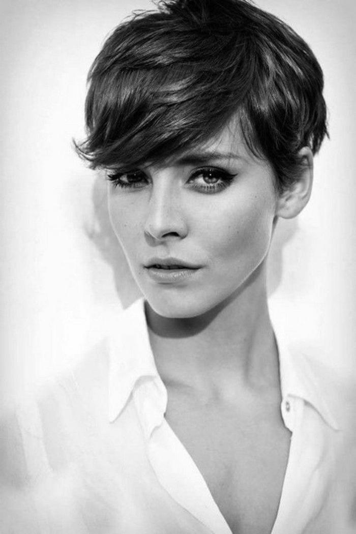 pelados modernos mujer con corte de pelo el pixie con flequillo hacia un lado, vestida con camisa blanca desabrochada