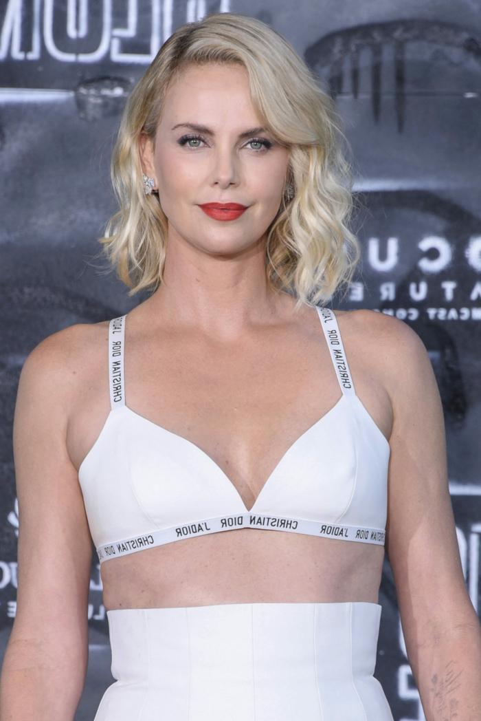 pelados modernos mujercon melena midi con flequillo rubia, vestida con pantalón de talla alta en blanco y top con inscripciones