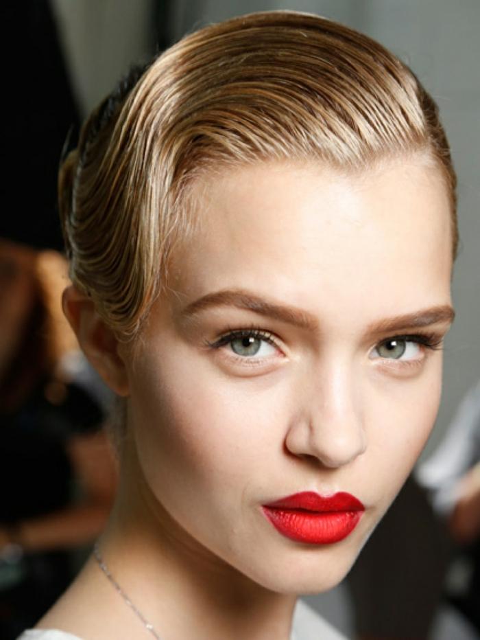 pelo corto con flequillo mujer rubia con pelo peinado al efecto mojado y flequillo echado hacia un lado, maquillada con labial rojo fuerte