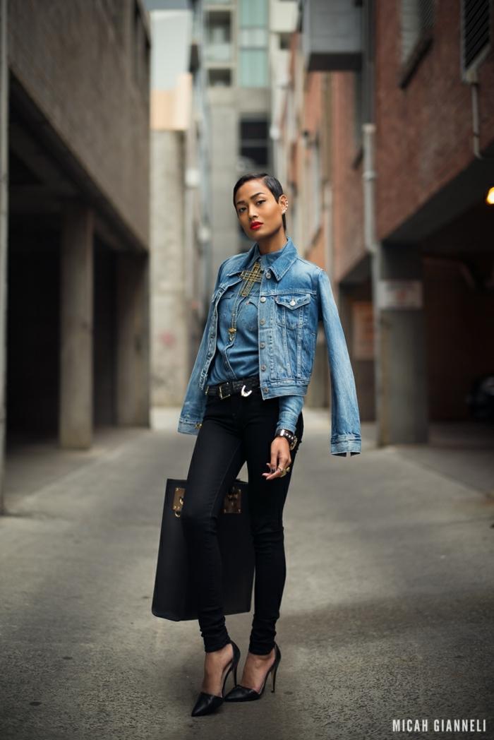 pelo corto ondulado mujer, peinado el pixie con cabello en color negro con chaqueta y camisa de jeans y colgante con un crucifijo grande