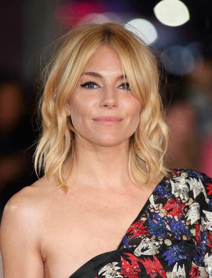 pelo corto ondulado mujer, rubia con melena midi con ondulaciones y vesntido multicolor de encaje con un hombro al descubierto