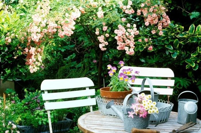 decoracion de jardines pequeños de encanto, muebles de madera, muchas macetas con plantas verdes