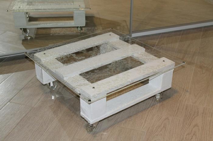 pequeña mesa cuadrada con vidrio encima sujeto con tapas metálicas y con ruedas transparentes, mesas con palets