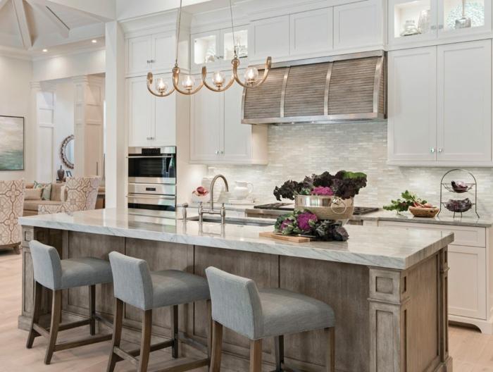 cocina con isla con encimera de mármol con armarios blancos y suelo de parquet en marrón claro