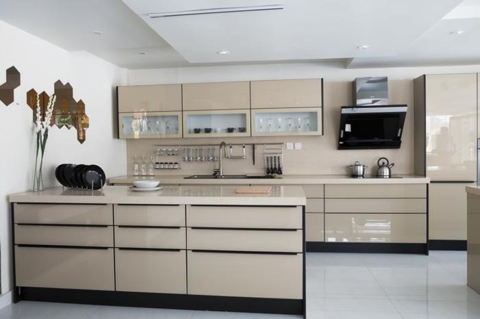 cocina de color beige brillante con decoración el la pared y platos negros puestos en la encimera