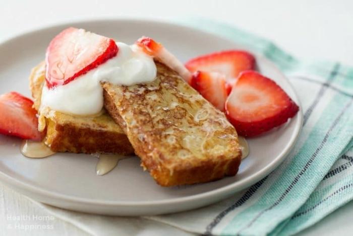tostadas fritas con miel, nata y fresas por encima en plato blanco, postres caseros faciles y rapidos