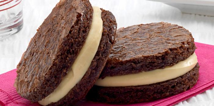 galletas de sandwich o brownies con crema de vainilla en mantel rosa, postres caseros faciles y rapidos