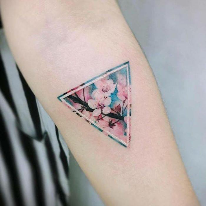 tatuaje triángulo tatuado en el antebrazo con flor de cereza coloridos, ideas tatuajes simbolicos