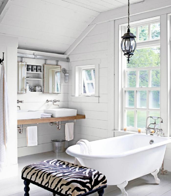 diseño de baños blanco y negro en estilo ecléctico, bañera exenta patas garra y banco tapizado estampado animal