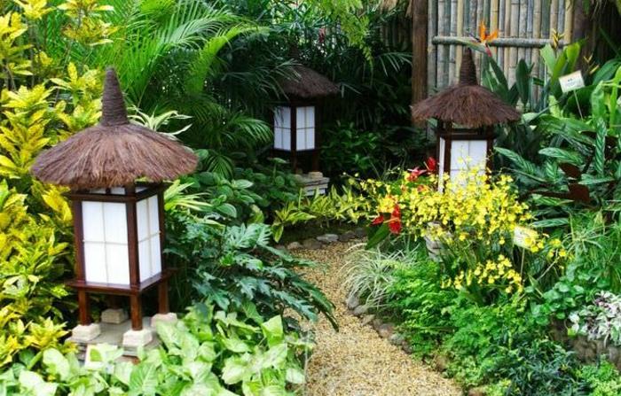 decoracion de jardines pequeños con mucha vegetación, suelo con gravilla y linternas decorativas