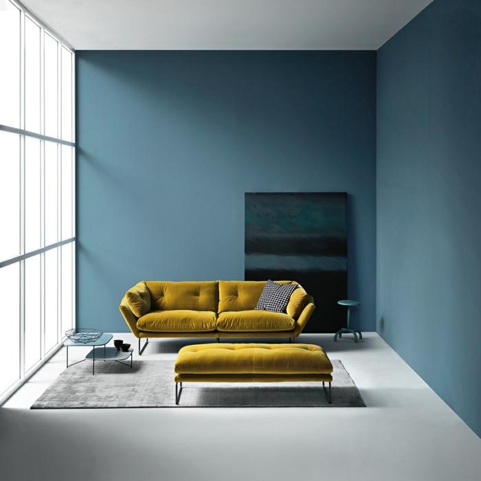 decoracion salon pequeño sofa de doble asiento en color mostaza y taburete alargado, con alfombra en gris y ventanas grandes