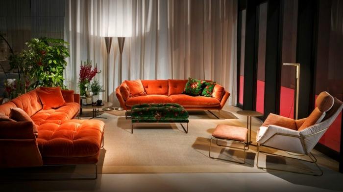 decoracion salon pequeño, con varios sofas de color coral de terciopelo con alfombra de marron clarito