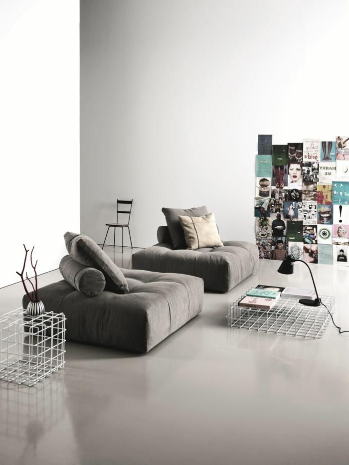decoracion salon pequeño decorado con sofa de suelo en gris oscuro con cojines cuadrados y de tubo, con imagenes en la pared