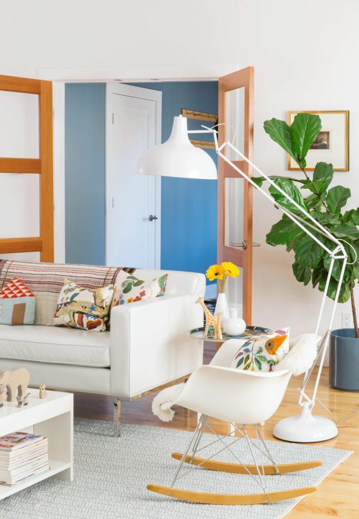 decoracion salon pequeño, sofa blanco bajito con cojines multicolores y de flores, lampara de pie blanca y mesita con jarrones