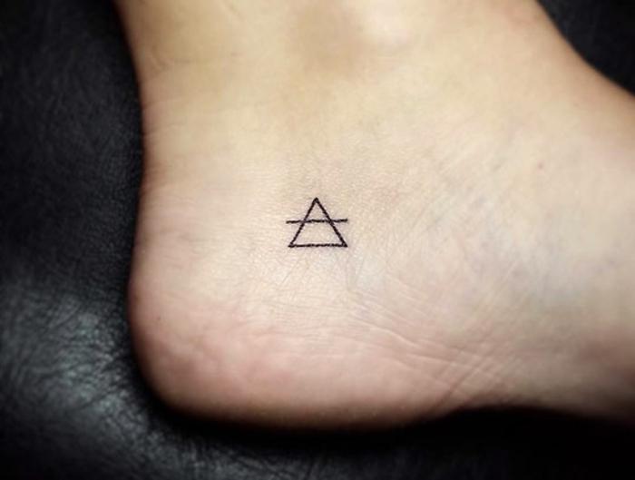 tatuajes simbolicos con triángulos, pequeño tiángulo en el pie con una línea, ideas tatuajes minimalistas