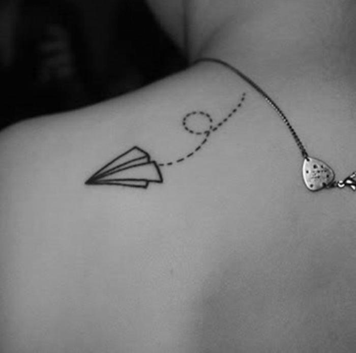 tatuajes discretos en la espalda con significado simbolico, avion de papel en vuelo tatuado en la espalda