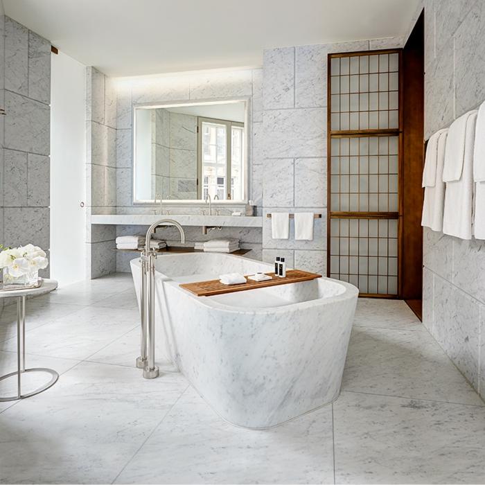 precioso baño de mármol, bañera de mármol, baldosas en blanco y gris, pequeña mesa auxiliar con flores