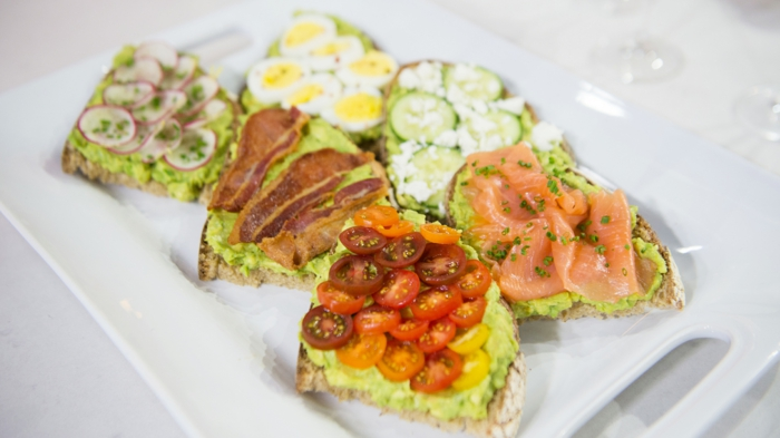 variantes de desayunos con aguacate, tostadas con aguacate machacado, salmón, tomates cherry, rabanos y tocino