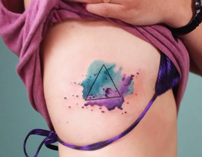 tatuajes simbolicos en acuarela, bonito triángulo tatuado en las costillas en azul y lila, tattoos geometricos mujer