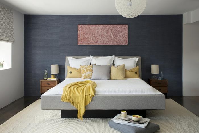 decoración de dormitorios, cama en gris de tela con cojines en amarillo, gris y blanco