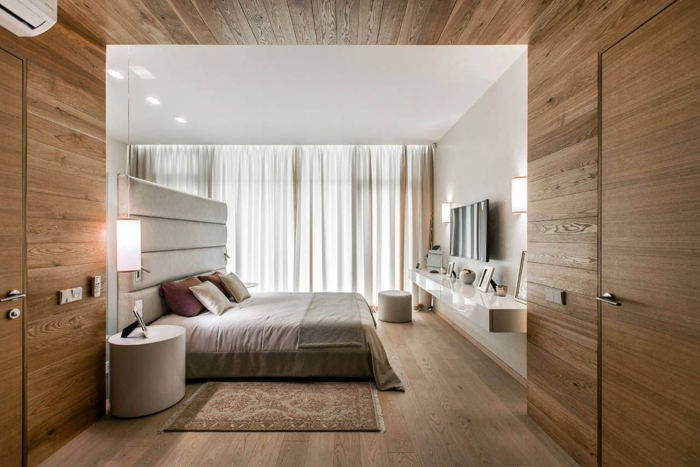 decoración de dormitorios, cama con cabecera alta en gris con cojines de diferentes colores, paredes blancas