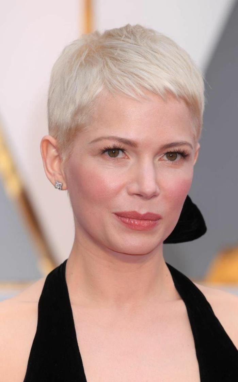 flequillo desfilado, mujer con corte de pelo corto con flequillo ultra corto, color rubio platino, con vestido negro