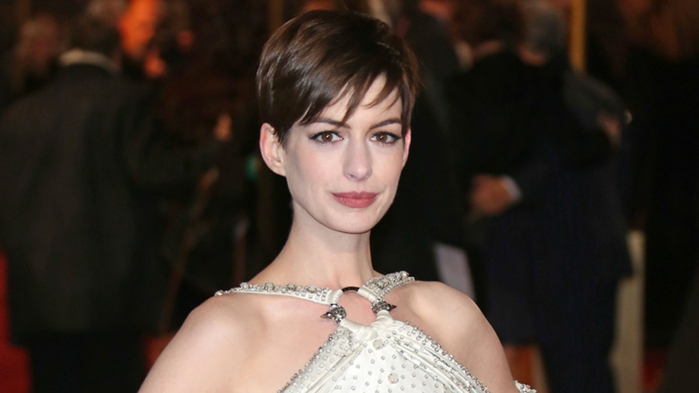 flequillo-desfilado, Anne Hathaway con el pelo corto, corte de chico con flequillo ladeado, con vestido blanco