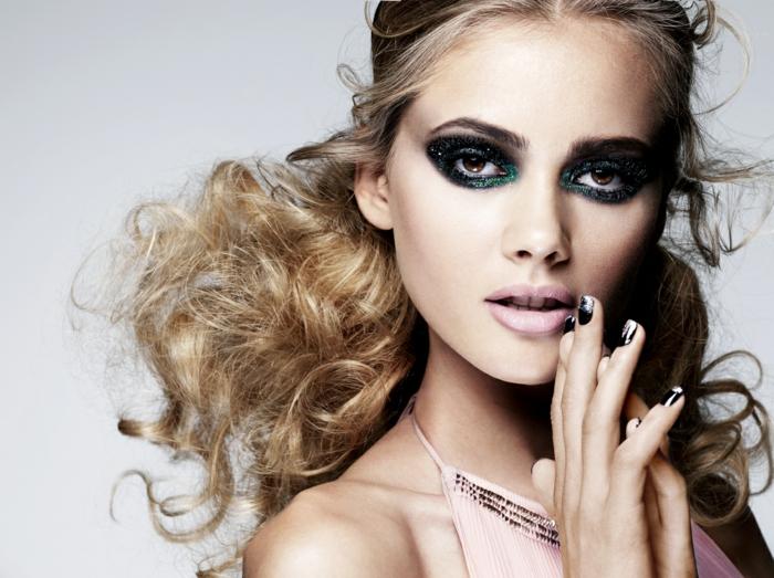 mujer con pelo rubio rizado recogido, maquillaje muy fuerte y uñas de gel decoradas en tonos oscuros, uñas francesitas con detalles