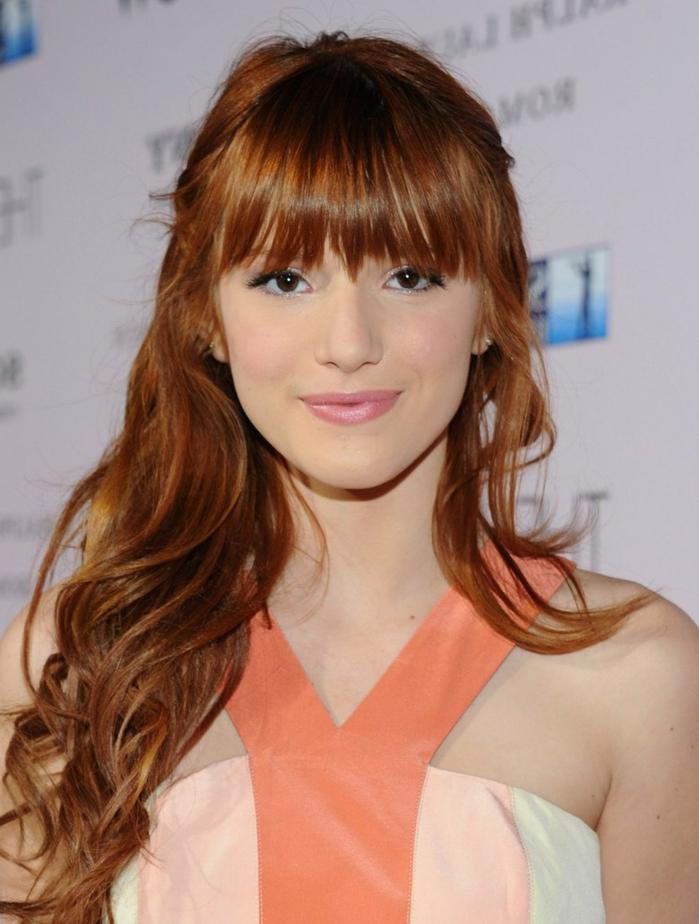 Peinados con flequillo, modelo con el pelo color cobre con ondulaciones y flequillo recto despeinado