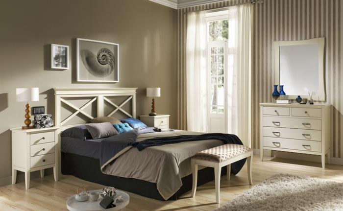 dormitorio con cama con cabecera cos aspas y sábanas en tonos marrones con cojínes en azul y mesas de noche