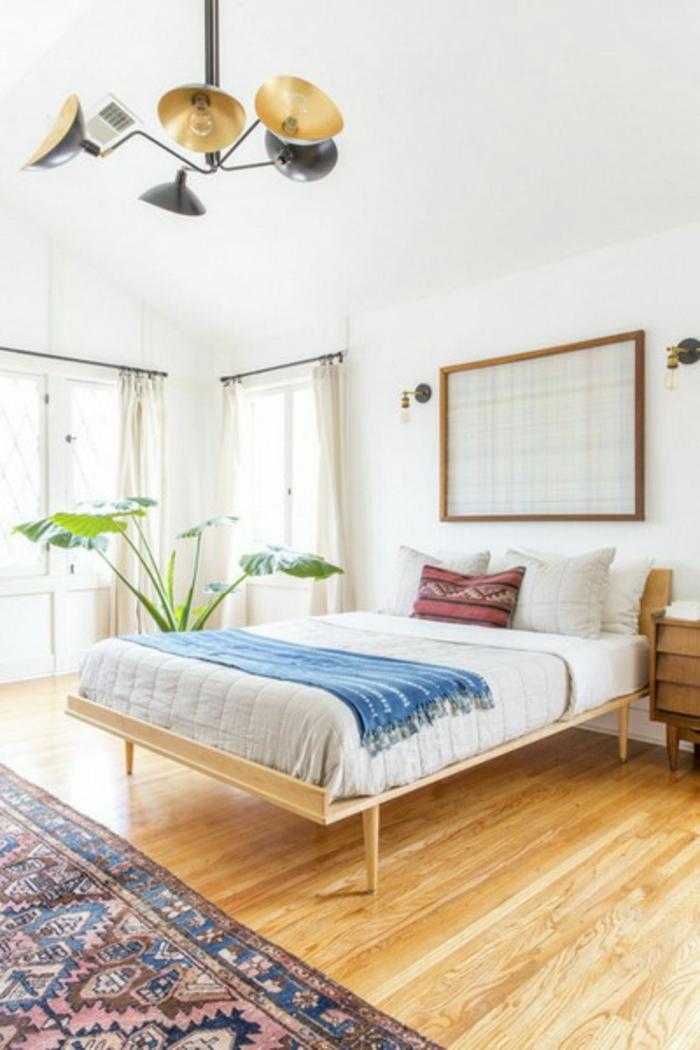 decoracion de dormitorio en estilo moderno con elementos boho chic, suelo de madera, paredes en blanco