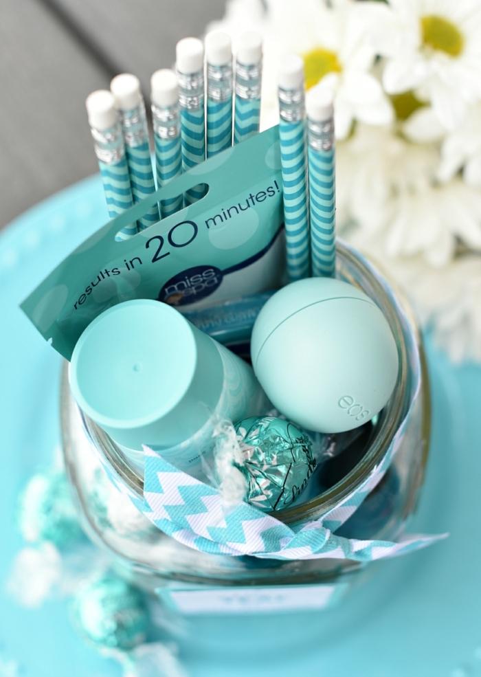 jarro de cristal con pequeños detalles en color azul, lapices, caramelos y crema para la piel