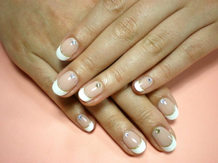 uñas de gel francesas con detalles en dorado, uñas largas con línea gruesa en blanco y cristales decorativos