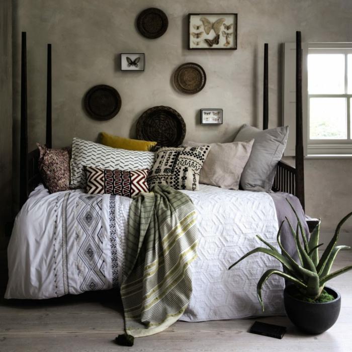 decoracion dormitorios en la estética bohemia, paredes en color ocre con mucha decoración, cojines decorativos y cactus