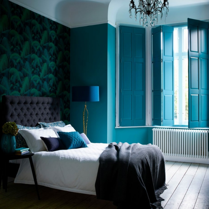 elegancia en color aguamarina, paredes con papel pintado estampado botánico, cama con cabecero en capitone