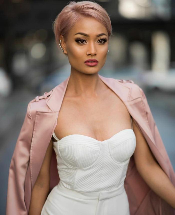 Modelo con corte de pelo corto con flequillo hacia un lado, color rosa, color de pelo para morenas