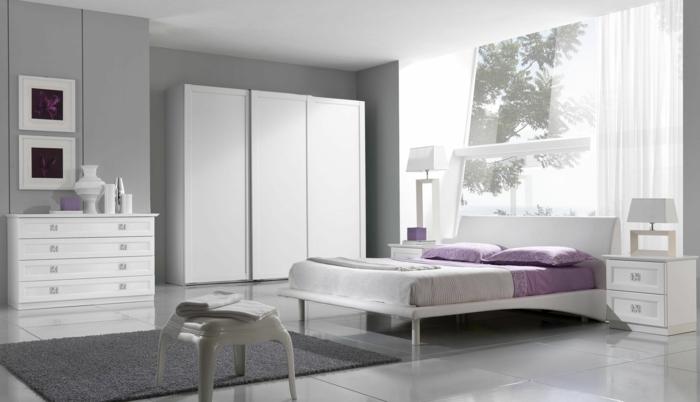 colores habitación paredes en gris con ventana grande, alfombra gris, muebles blancos, cuadros en lila