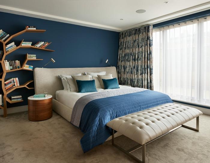 estanterías originales para decoracion dormitorios, grande cama en beige, pie de cama en capitoné y pared en azul intenso