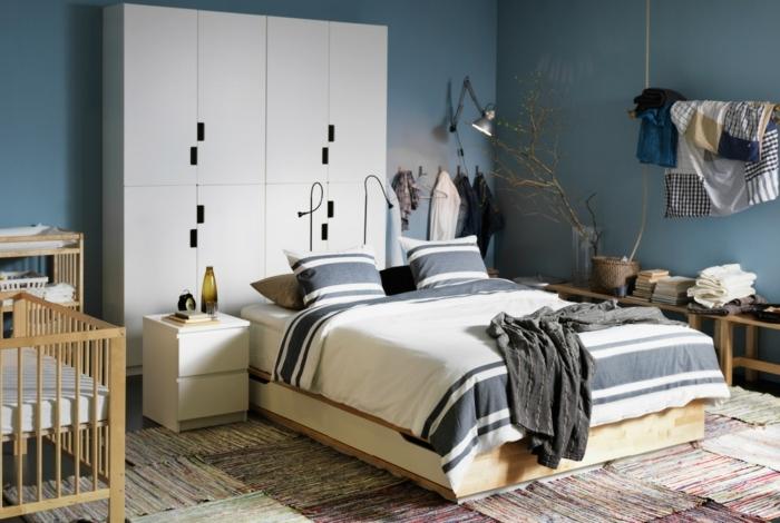 como pintar una dormitorio con paredes azules, armario en blanco, alfombras y cuna en la izquierda
